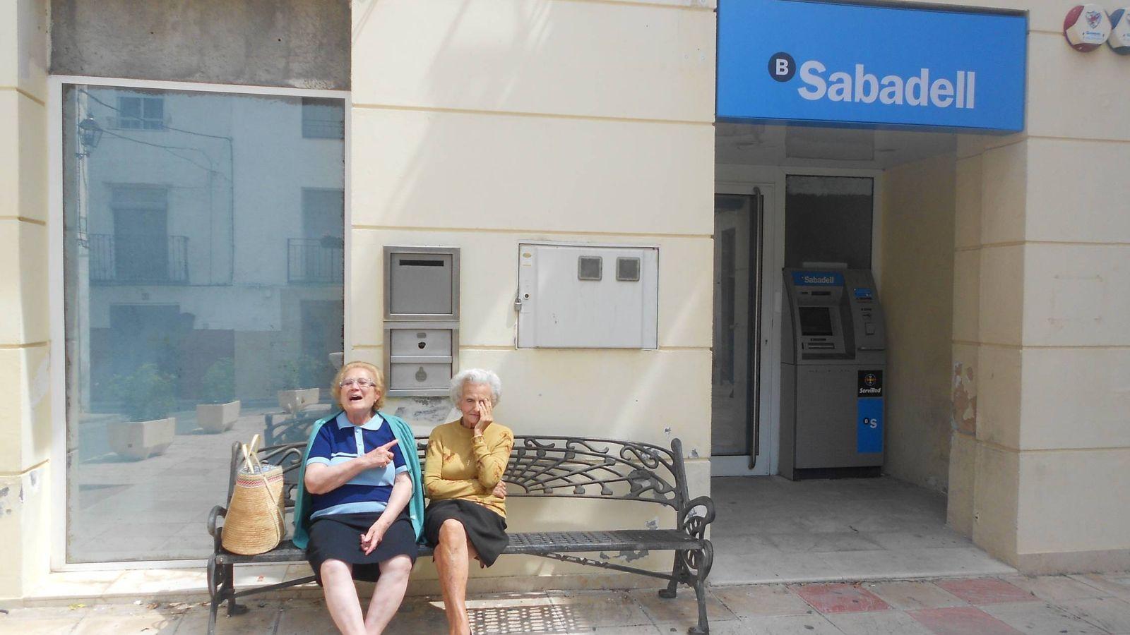 Foto: Dos jubiladas de Benilloba, sentadas a las puertas de la oficina que acaba de cerrar. (V. R.)