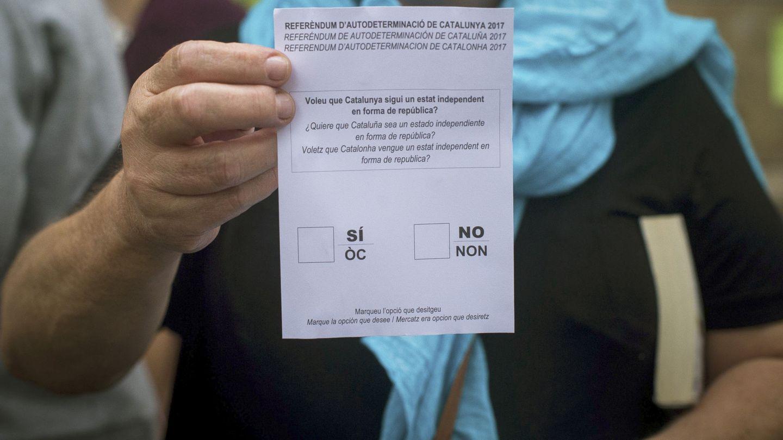 Una mujer muestra una papeleta del referéndum del 1-O en un colegio de Barcelona donde se están haciendo actividades para mantenerlo abierto. (EFE)