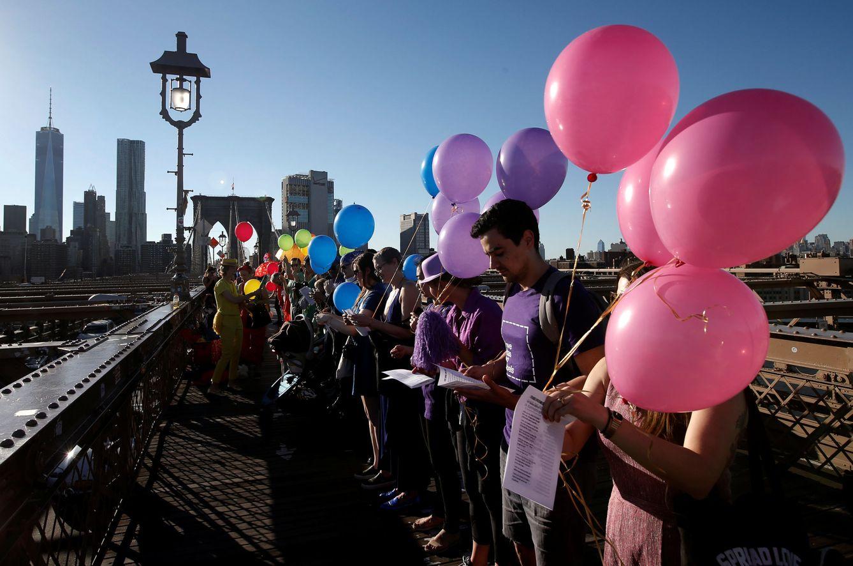 Foto: Neoyorquinos sostienen globos durante un homenaje a las víctimas de la masacre de Orlando en el Puente de Brooklyn, el 14 de junio de 2016 (Reuters).