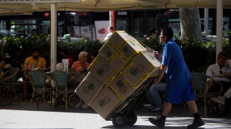 Un hombre transporta cajas en el centro de Barcelona. (EFE)