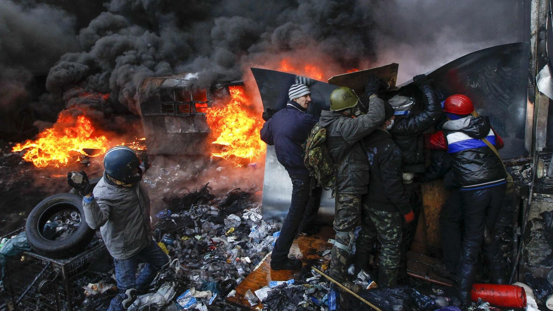 Manifestantes arrojan piedras contra los antidisturbios en Kiev (Reuters).