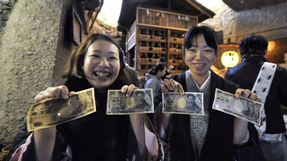 Foto: Dos jóvenes japonesas 'purifican' sus billetes con agua sagrada para atraer la suerte. (EFE)