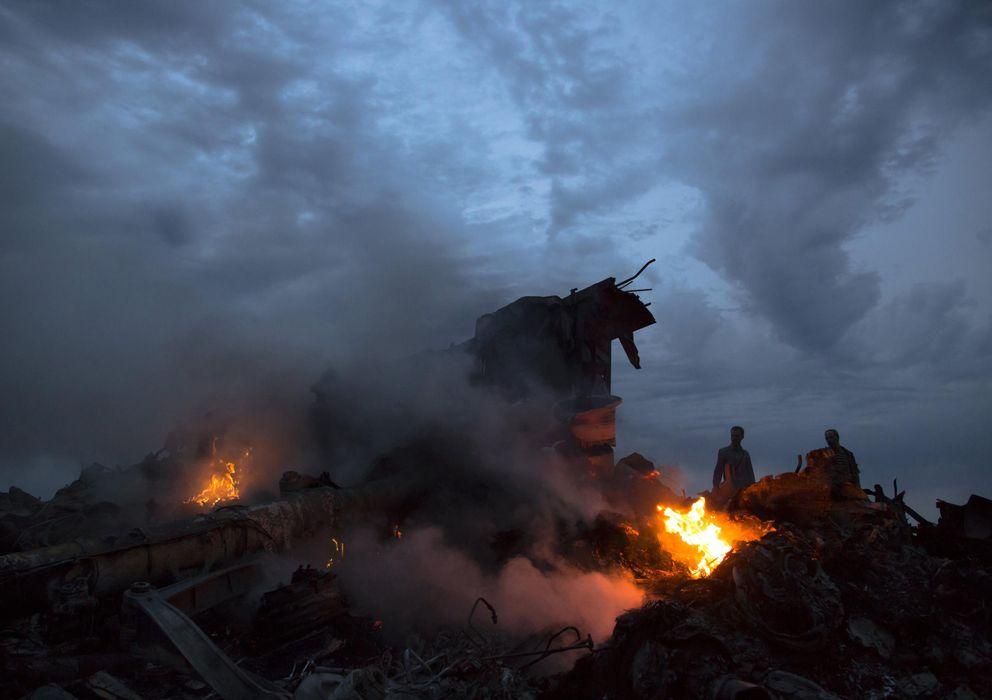 Foto: Un grupo de personas camino entre los restos del avión malasio derribado en el Este de Ucrania (AP).