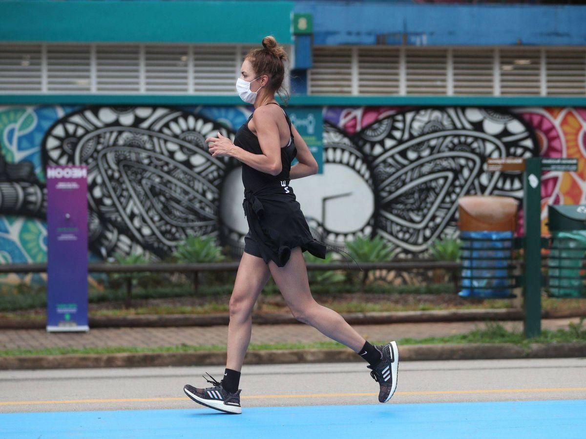 Foto: Una mujer hace ejercicio en la vía pública con mascarilla. (EFE)
