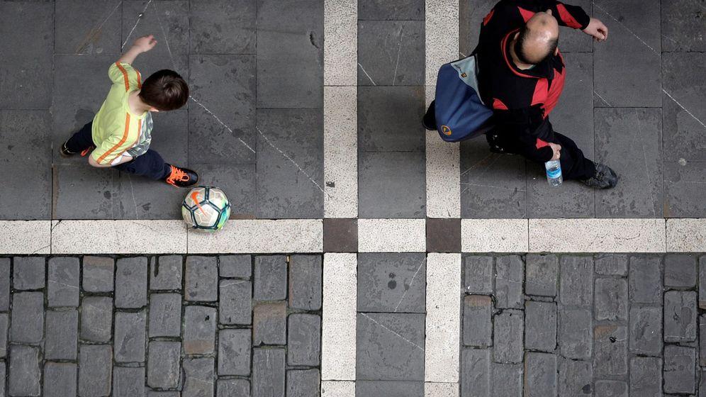 Foto: Un niño con un balón camina junto a un adulto en horario infantil. (EFE)