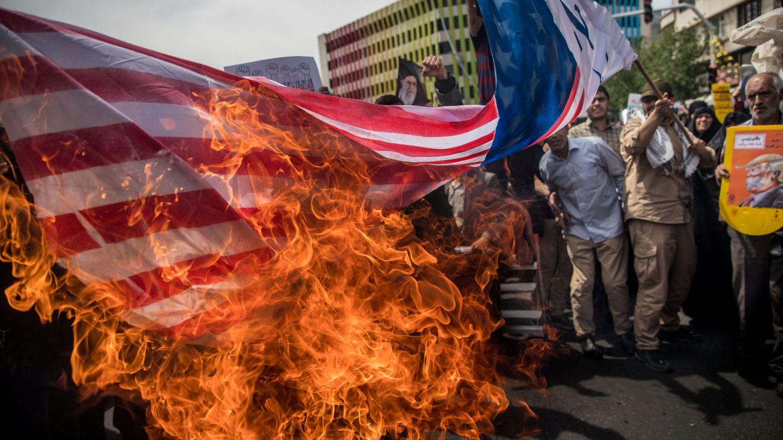 Manifestantes iraníes queman banderas de EEUU como protesta por su retirada del acuerdo nuclear, en Teherán, el 11 de mayo de 2018. (Reuters)