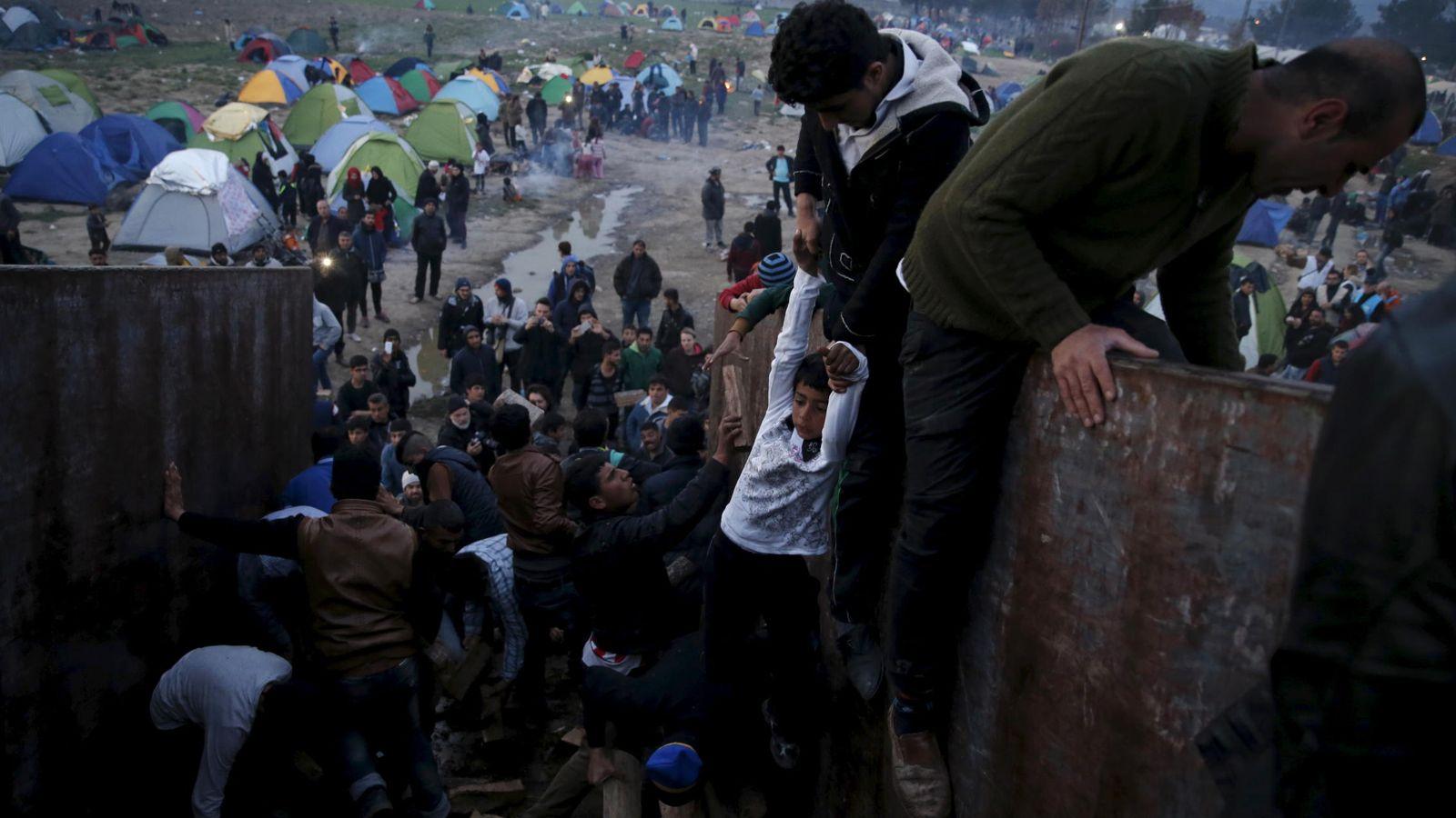Foto: Migrantes y refugiados atrapados en la frontera entre Grecia y Macedonia intentan conseguir madera, cerca de Idomeni, el 6 de marzo de 2016 (Reuters).