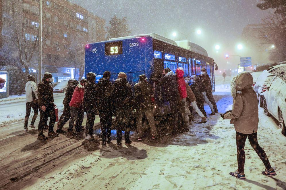 Foto: Varias personas empujan un autobús atascado en la nieve. (EFE)