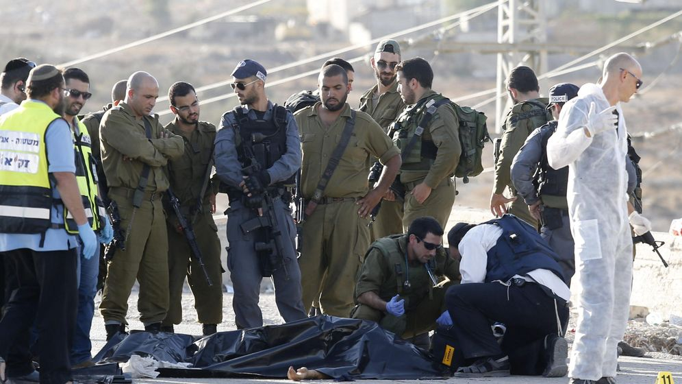 Foto: Varios policías israelíes recopilan pruebas junto al cuerpo sin vida de un palestino que ha sido abatido a tiros por un soldado israelí. (Efe)