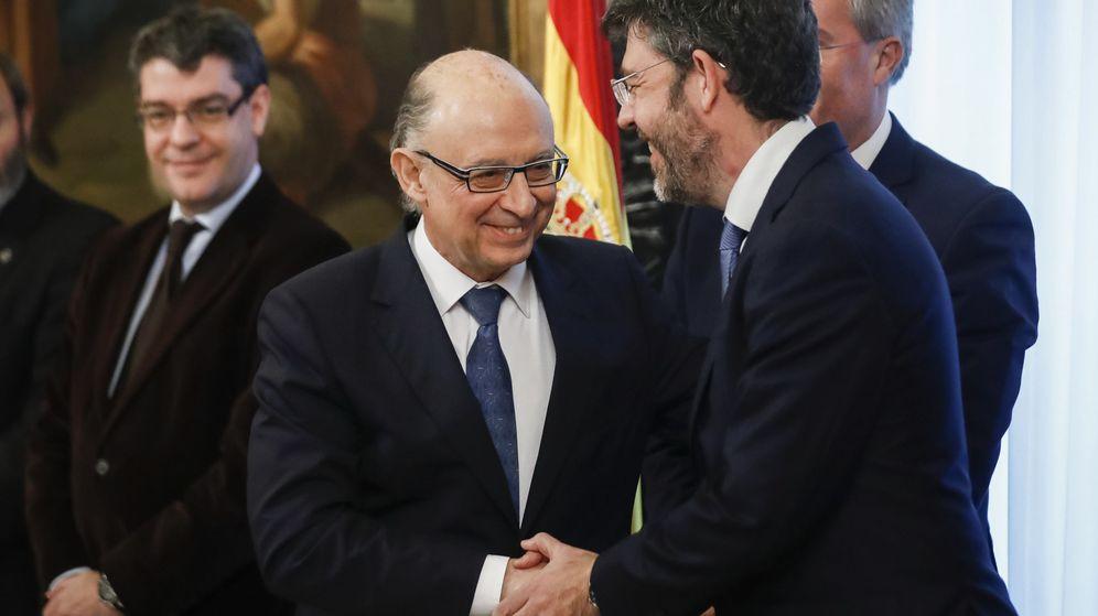 Foto: El ministro de Hacienda y Función Pública, Cristobal Montoro (i), felicita al secretario de Estado de Presupuestos y Gastos, Alberto Nadal, tras jurar su cargo. (EFE)