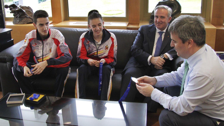 El expresidente del CSD, Miguel Cardenal (d), observa una de las medallas de los taekwondistas Jesús Tortosa Cabrera (i) y Lidia García Auñón (2i), junto a Castellanos. (EFE)