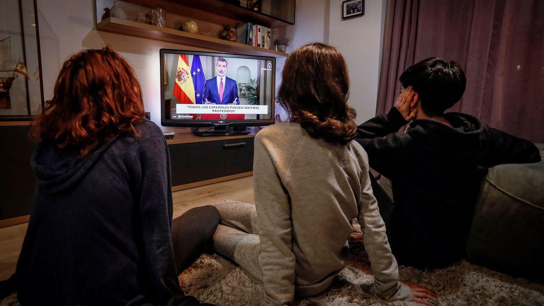 Tres personas ven el discurso extraordinario de Felipe VI. (EFE)