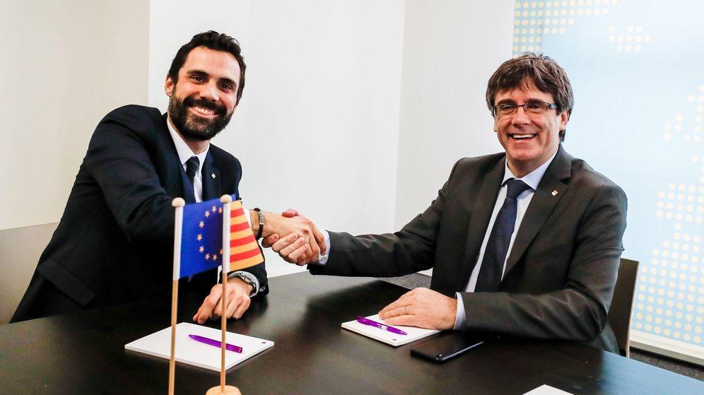 Foto: El expresidente de la Generalitat Carles Puigdemont (d) estrecha la mano del presidente del Parlamento autónomo, Roger Torrent. (EFE)