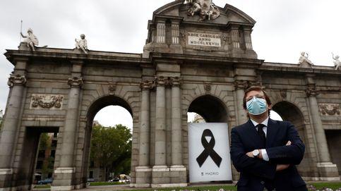 Madrid recuerda a los muertos por covid-19 con un crespón en la Puerta de Alcalá
