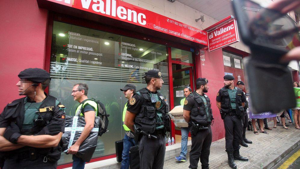 Foto: Efectivos de la guardia civil transportan cajas a su salida del semanario 'El Vallenc'. (EFE)