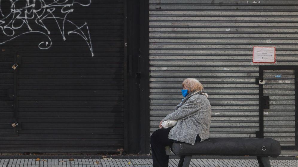 Foto: Mujer frente a un establecimiento cerrado. (EFE)