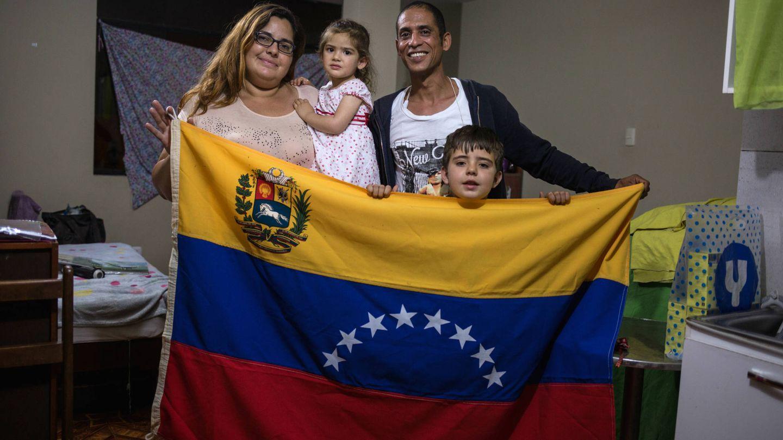 La familia posa con una bandera venezolana en su apartamento. (L. Arango)