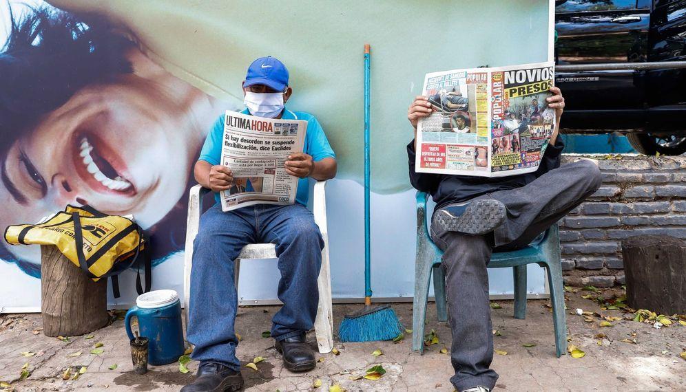 Foto: Dos hombres leen el periódico al aire libre este lunes, en Asunción (Paraguay). (EFE)