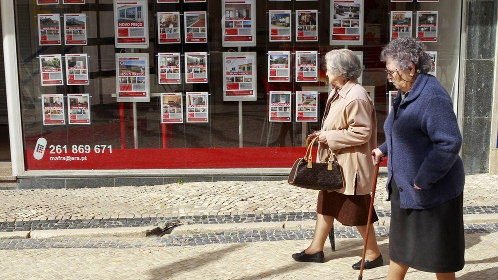 Foto: Dos mujeres pasan delante de una inmobiliaria en Ericeira. (Reuters)