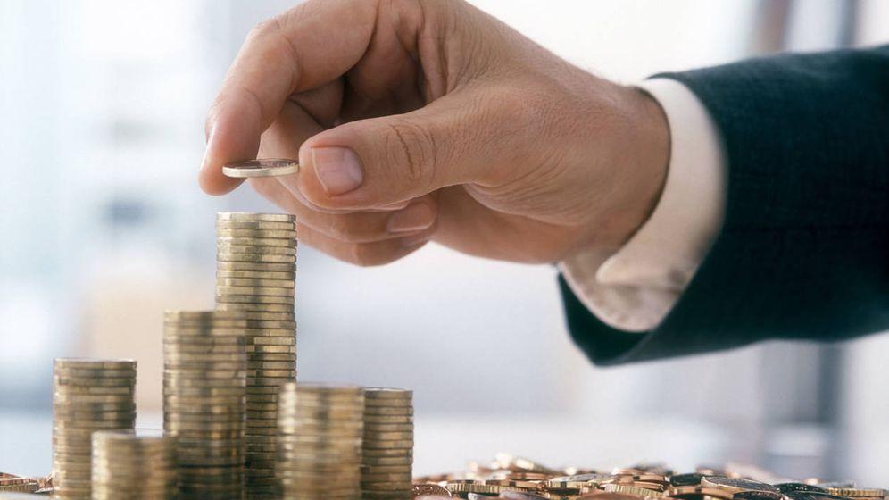Foto: Un hombre deposita una moneda sobre otra. (iStock)