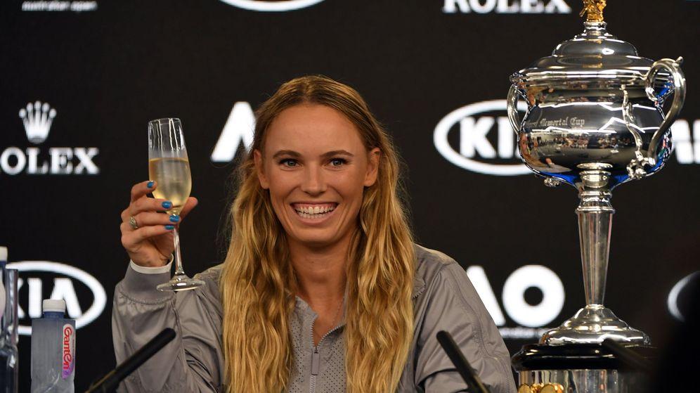 Foto: Wozniacki se presentó en la rueda de prensa con una copa de champán y el trofeo del Open de Australia. (EFE)