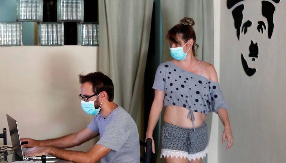Foto: Dos jóvenes usan tapabocas dentro de su casa, durante la cuarentena por el coronavirus. EFE