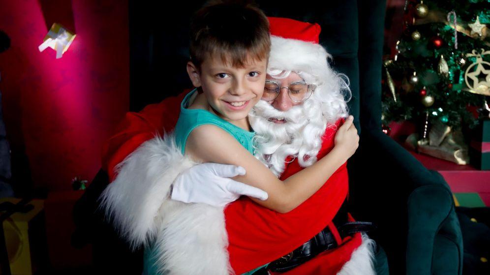 Foto: Un niño abraz a Papá Noel en un parque navideño de Buenos Aires (Argentina)