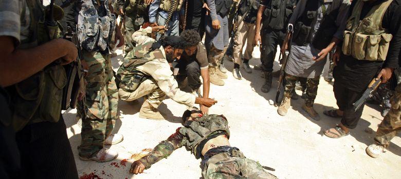 Foto: Combatientes del Ejercito de Liberación Sirio inspeccionan un cadáver durante una ofensiva en Alepo (Reuters).
