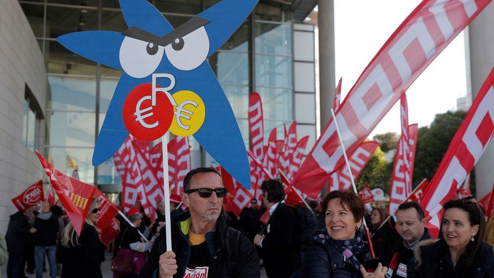 Foto: Sindicalistas protestan contra el ERE en la junta de CaixaBank (EFE)