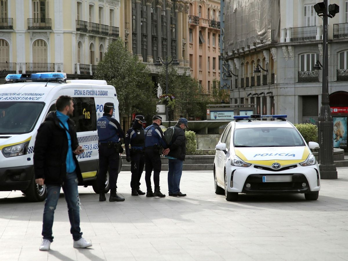 Foto: Miembros de la policía Municipal esposan a un viandante que incumplía la cuarentena. (EFE)