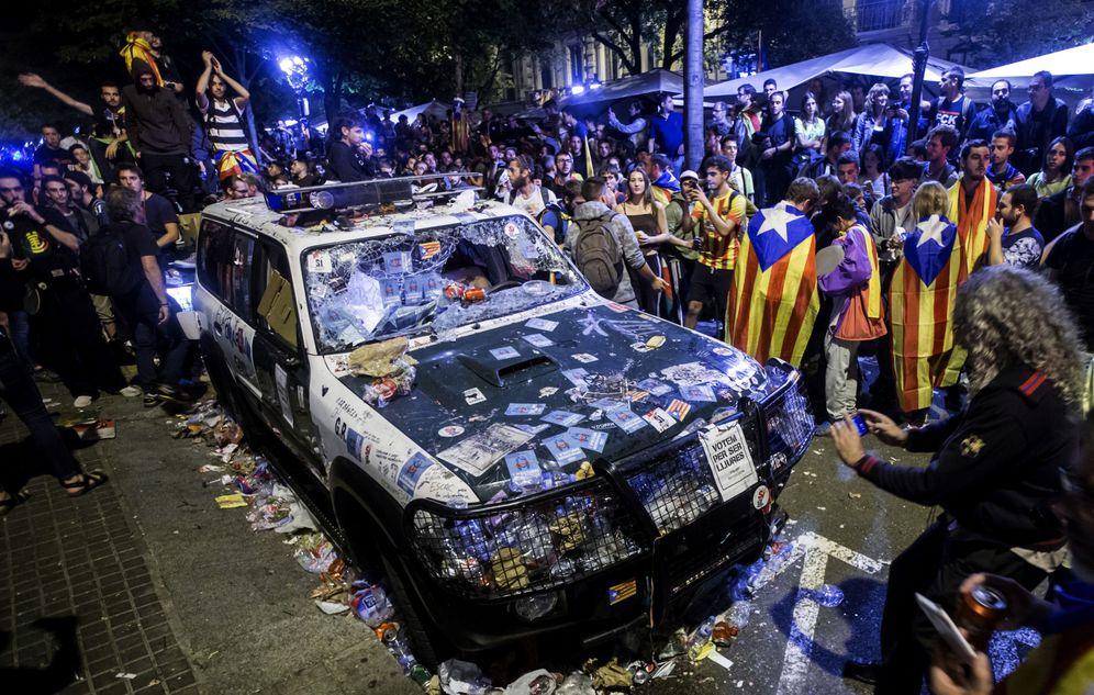 Foto: Numerosas personas rodean un coche de la Guardia Civil destrozado y repleto de pegatinas que realizaba un registro en la Conselleria de Economía con motivo del 1-O. (EFE)