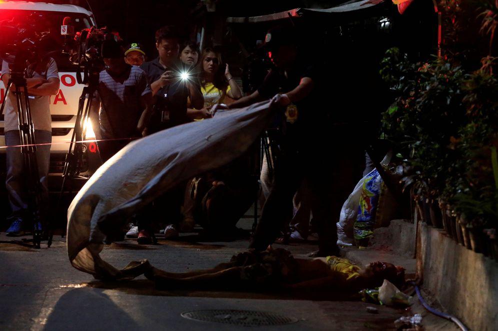 Foto: Agentes tapan el cadáver de un presunto traficante abatido por la policía, en Quezon, Metro Manila. (Reuters)