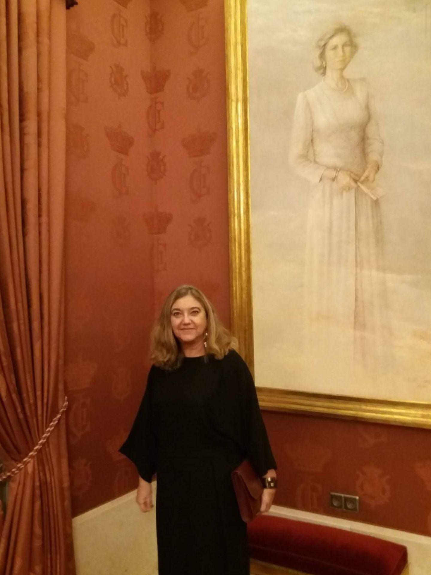 La autora, junto a un retrato de la reina Sofía. (Foto cedida)