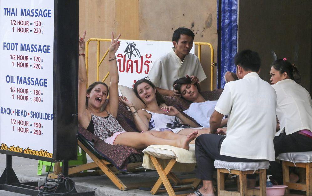 Foto: Turistas disfrutan de un masaje en una calle en Bangkok, Tailandia (EFE)