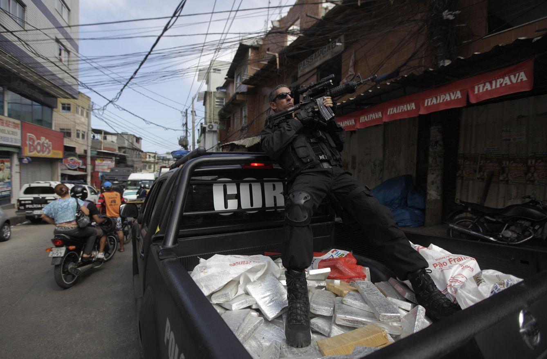 Foto: Un agente de policía apunta con su arma sentado sobre paquetes de marihuana confiscados durante una operación en la favela de Rocinha, en Río (Reuters).