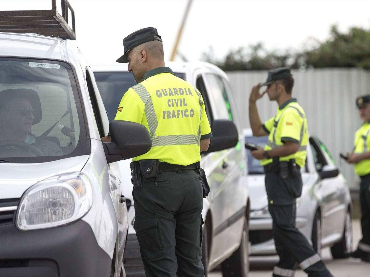 Foto: Agentes de la Guardia Civil de Tráfico inspeccionan la documentación de un grupo de conductores.