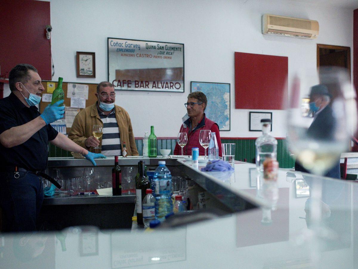 Foto: Varios clientes conversan en el interior de una bar de Ourense. (EFE)