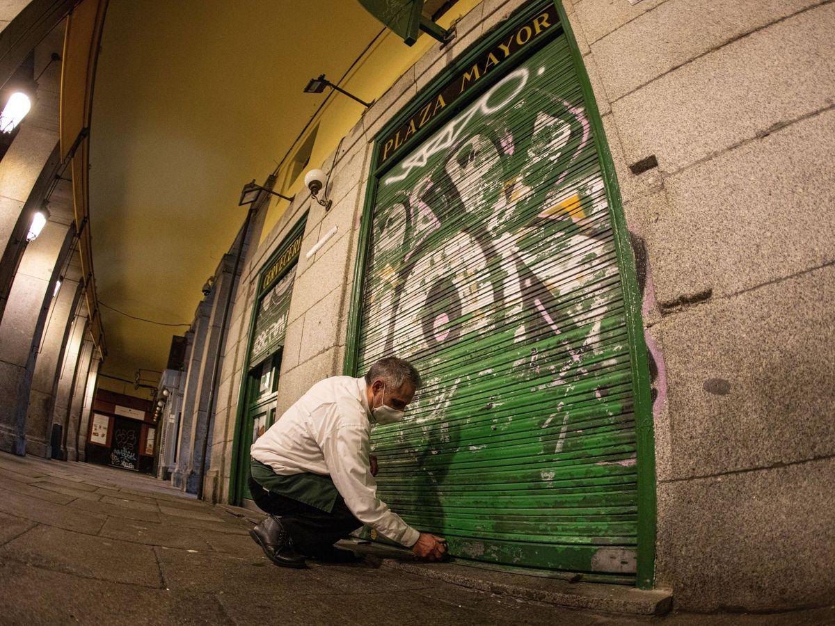 Foto: Un hombre cierra un negocio en Madrid. (EFE)