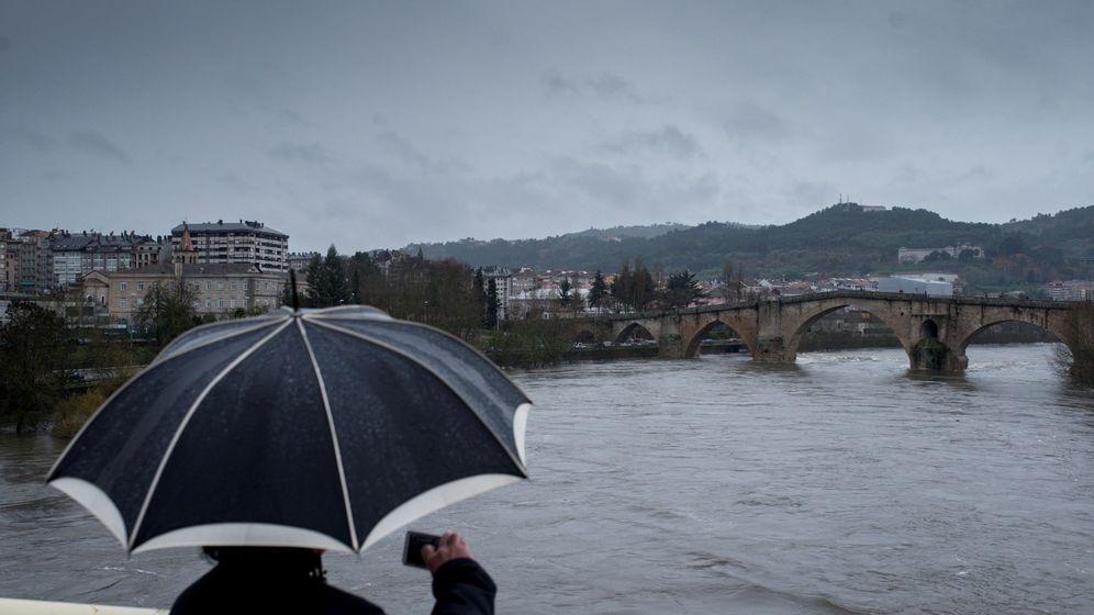 Foto: Un hombre fotografía el caudal del río Miño a su paso por Ourense. (EFE)