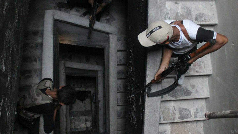 Combatientes del ejército de liberación sirio se ponen a cubierto dentro de un edificio en alepo (reuters).