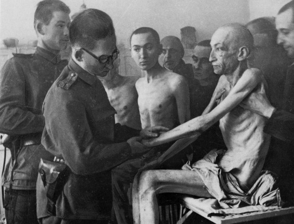 Foto: Un militar sanitario de la 'Armada Roja' soviética examina a uno de los supervivientes de Auschwitz tras su liberación el 27 de enero de 1945