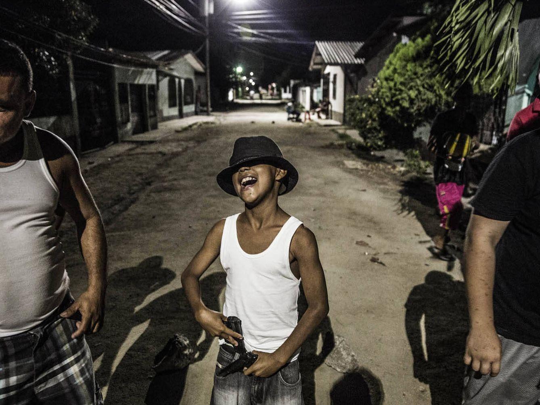 Foto: Un miembro de los Vatos Locos juega con una pistola antes de posar junto al grupo. Desde que nacen, según la zona, ya pertenecen a la pandilla del barrio (Foto: Javier Arcenillas).