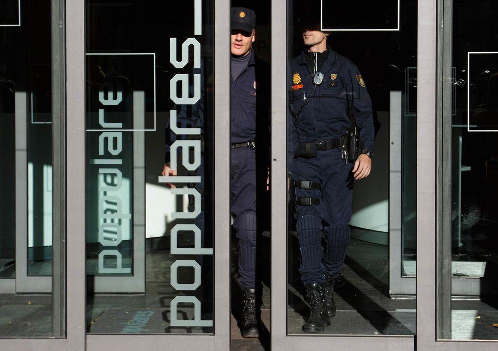 Foto: Dos policías salen de la sede del PP en la calle Génova de Madrid. (Reuters).