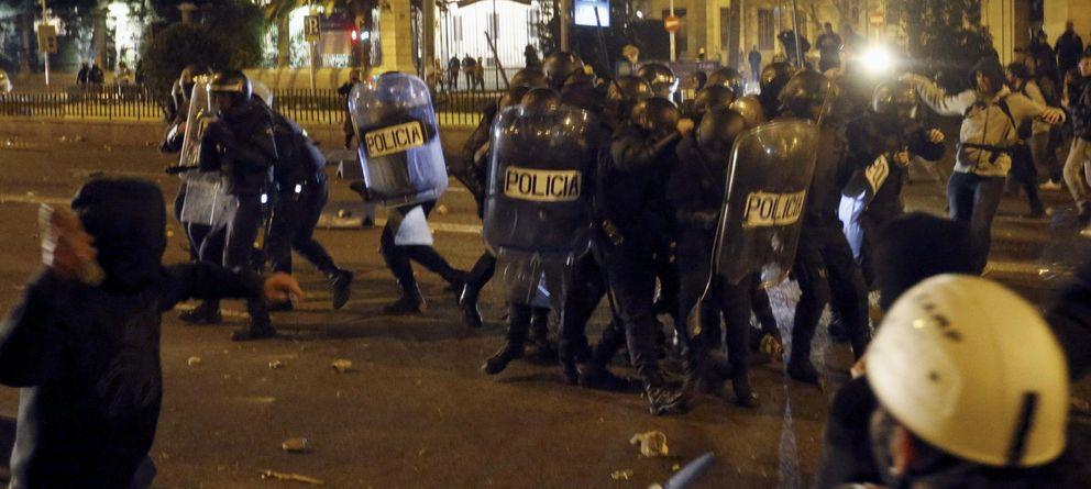 Foto: Policías antidisturbios se protegen en las inmediaciones de la Plaza de Cibeles (Efe)