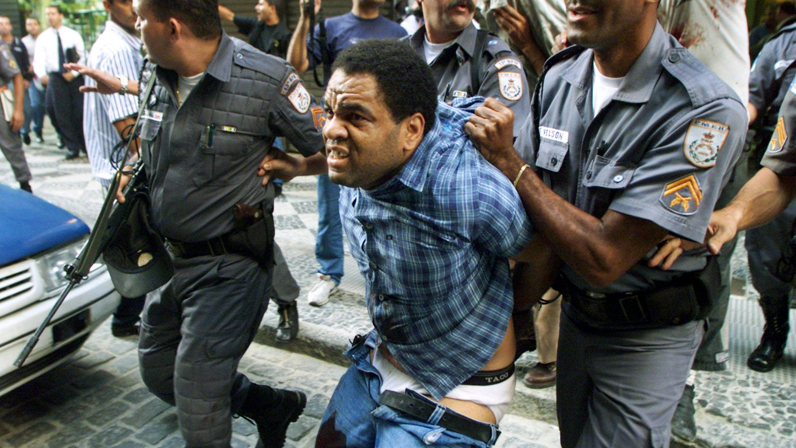 Foto: La policía se lleva a un atracador herido para evitar que la multitud lo linche, en Río de Janeiro, en octubre de 1999. (Reuters)