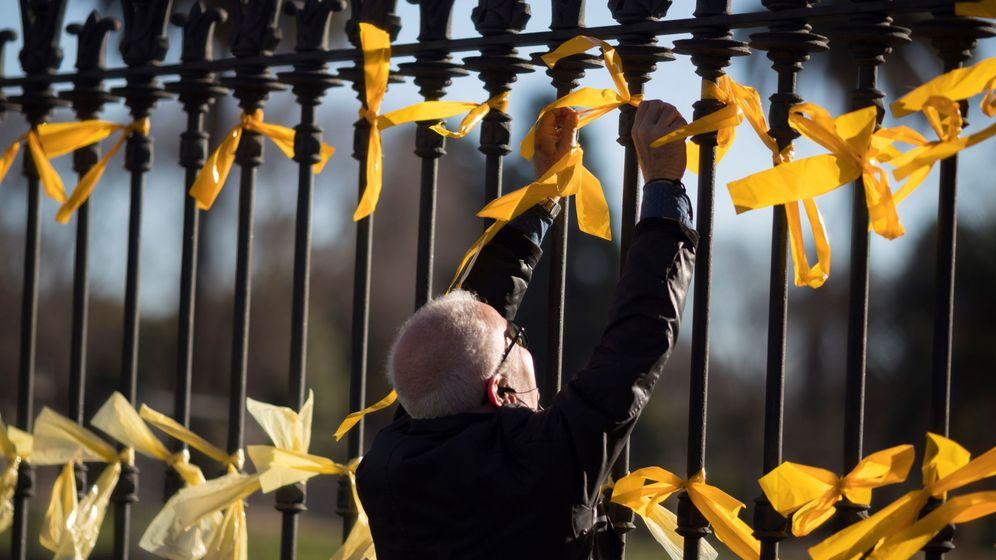 Foto: Un hombre coloca lazos amarillos en la verja del Parc de la Ciutadella en Barcelona. (EFE)
