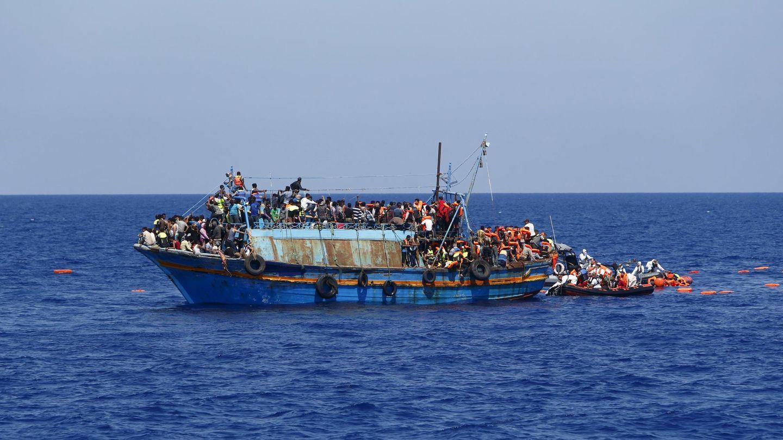 Inmigrantes en una patera a punto de volcar siendo rescatados frente a las costas de Libia. (Reuters)