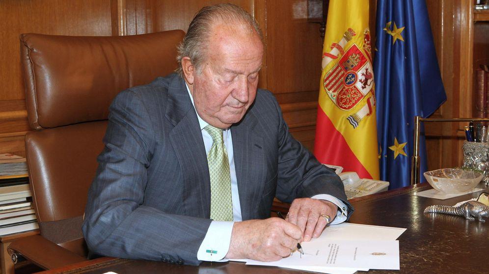 Foto: El rey Juan Carlos firmando el documento de su abdicación en 2014. (EFE)