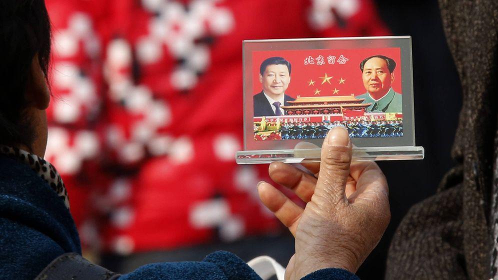 Foto: Un vendedor callejero muestra un souvenir con las fotos de Xi Jinping y Mao Zedong en la plaza de Tiananmen de Pekín, en noviembre de 2013. (Reuters)