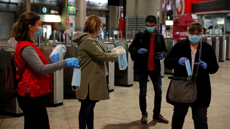 Varias personas reparten este lunes en la estación de Atocha mascarillas. (EFE)